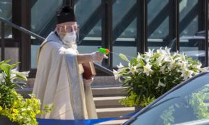 Detroit Priest Sprays Holy Water From Squirt Gun To Maintain Social Distancing